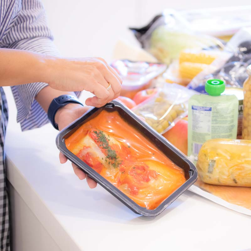 Woman opening pre-cooked food packaged in performance packaging.
